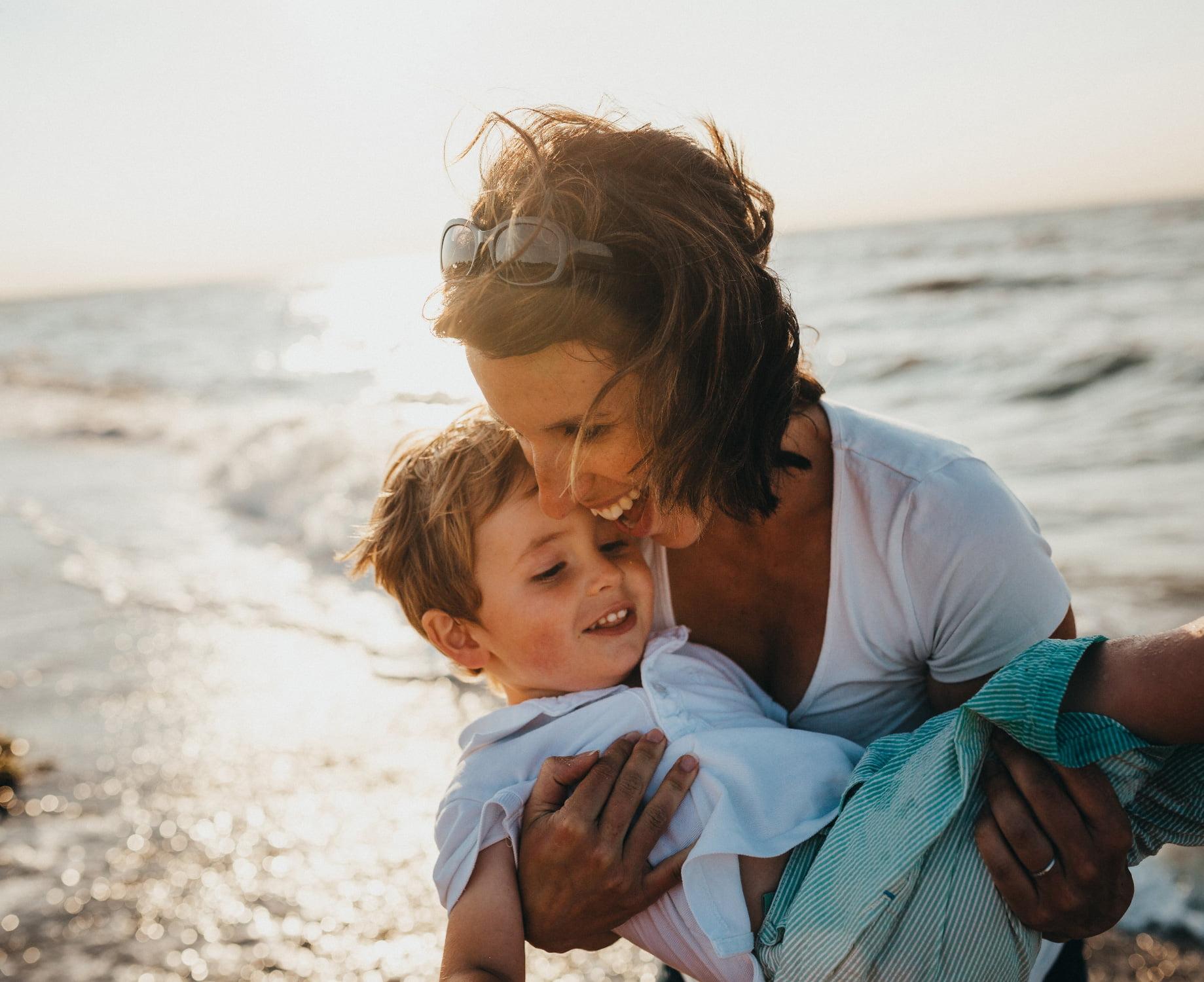 nainen kantaa lasta sylissään, kummatkin nauravat
