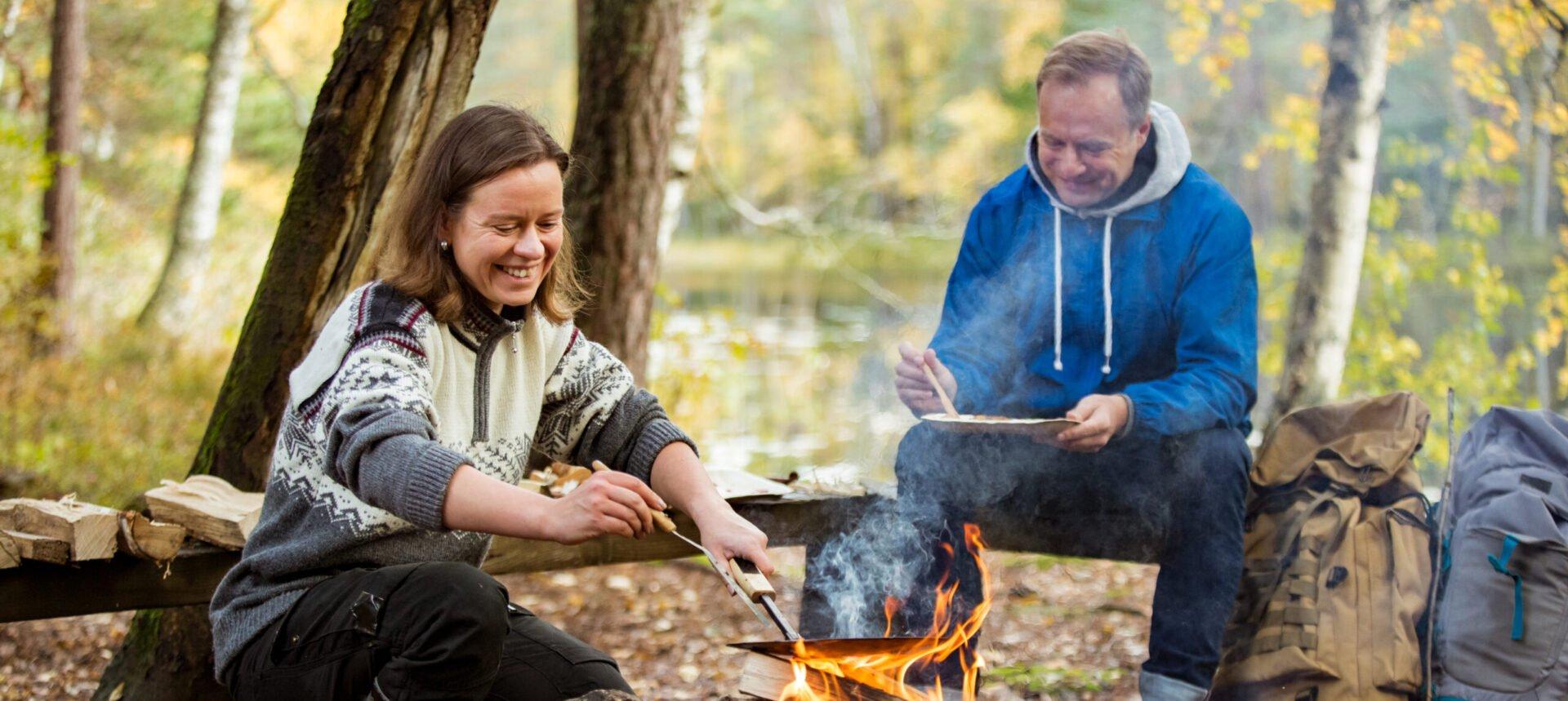 mies ja nainen tekevät ruokaa nuotion äärellä