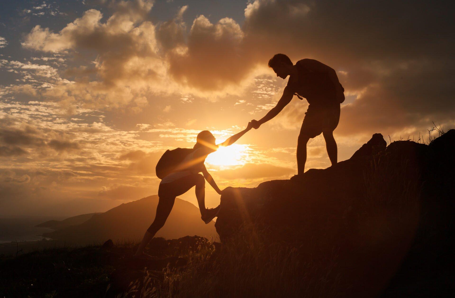 kiipeilijä auttamassa toista auringonlaskussa
