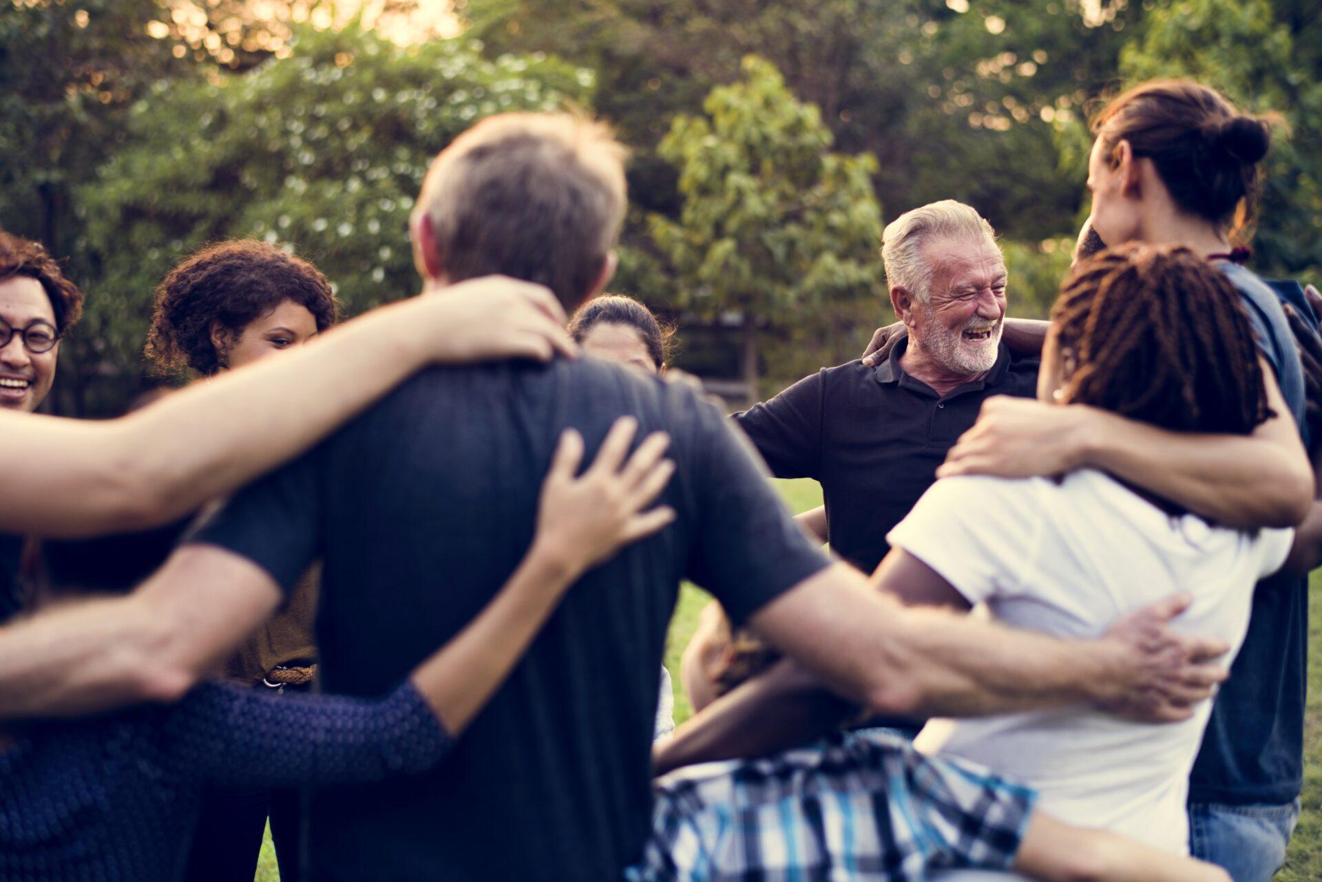 Järjestöt tukemassa toisiaan. Joukko ihmisiä seisoo ringissä ja lepuuttaa kättään toistensa olkapäillä.