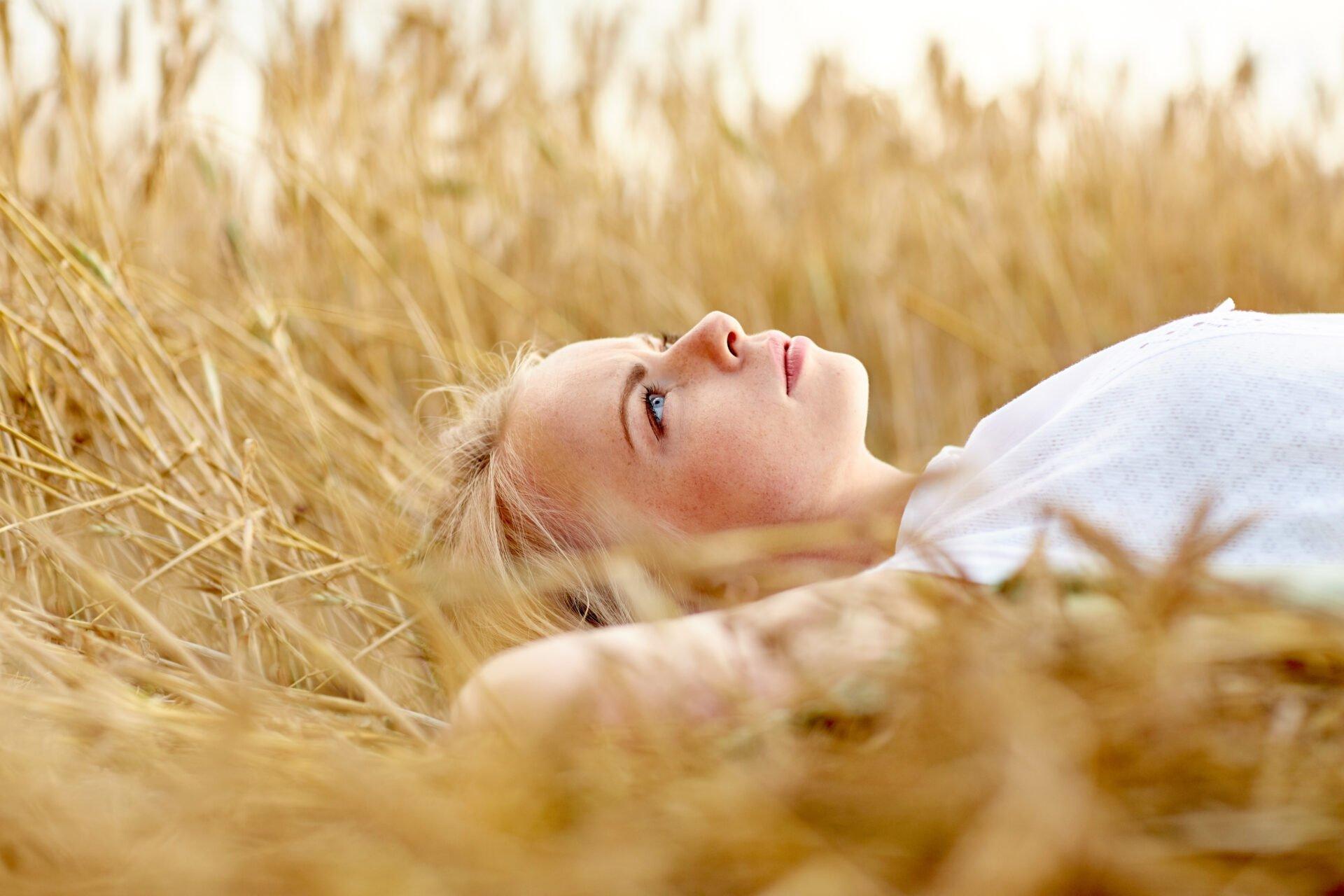 Hyväntekeväisyyskö itsekästä? artikkelin pääkuva, jossa nainen makaa viljapellolla pohdiskelevan näköisenä.
